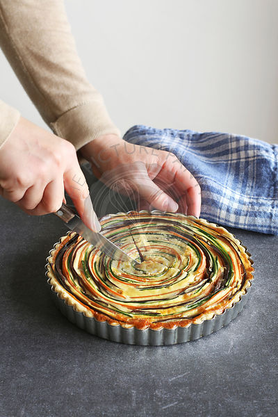 Female hands slicing a vegetable tart