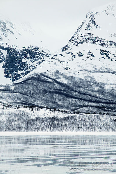 Snow-capped mountains and half-frozen fjord