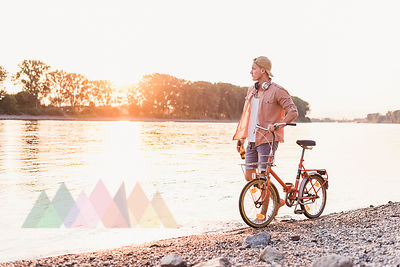 Young man walking with bicycle at the riverbank at sunset
