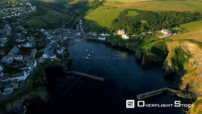 Drone pulls back at height to reveal the harbor of Port Isaac in Cornwall during the golden hour