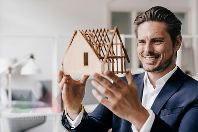 Smiling architect examining architectural model