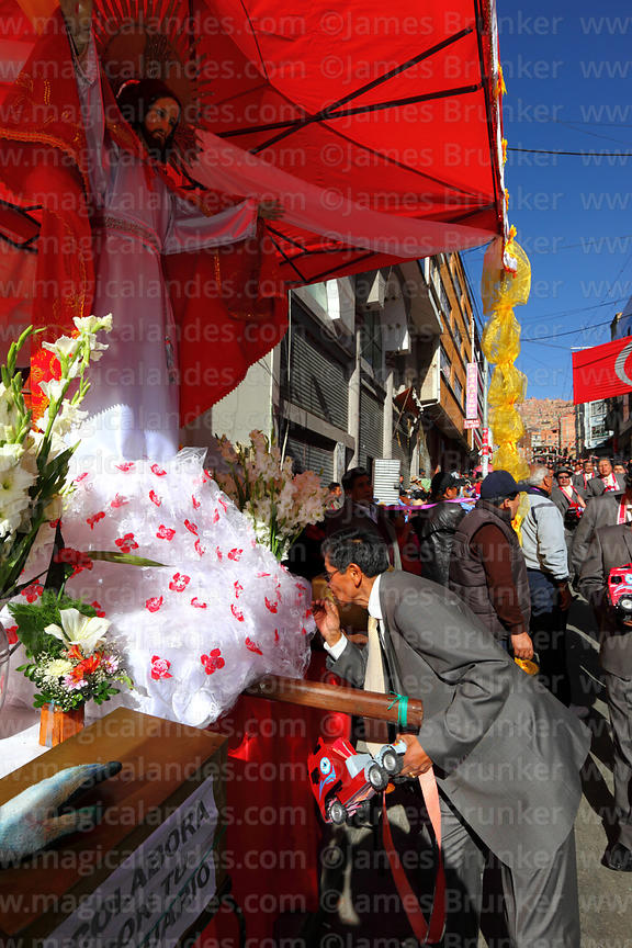 A member of the Heavy Transport Union morenada group pays his repects to the Señor del Gran Poder, La Paz, Bolivia