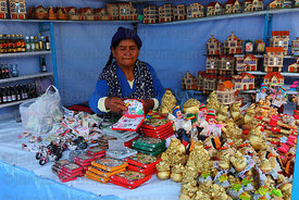 Woman arranging miniatures on her stall at start of Alasitas festival, La Paz, Bolivia