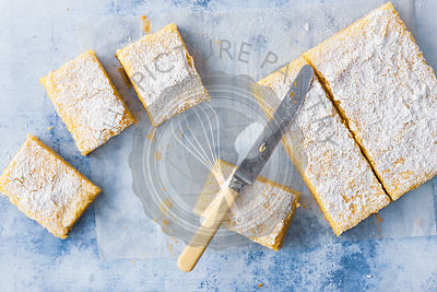 Homemade lemon slice dusted with icing sugar and cut into pieces.