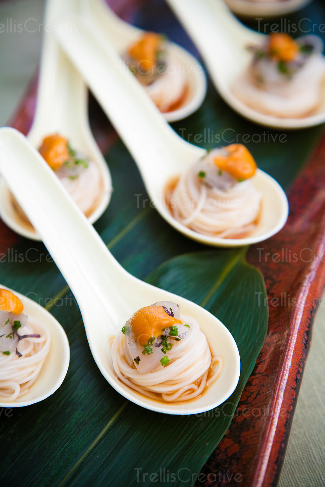 Swirrled udon noodles displayed on ivory spoons at a wedding reception