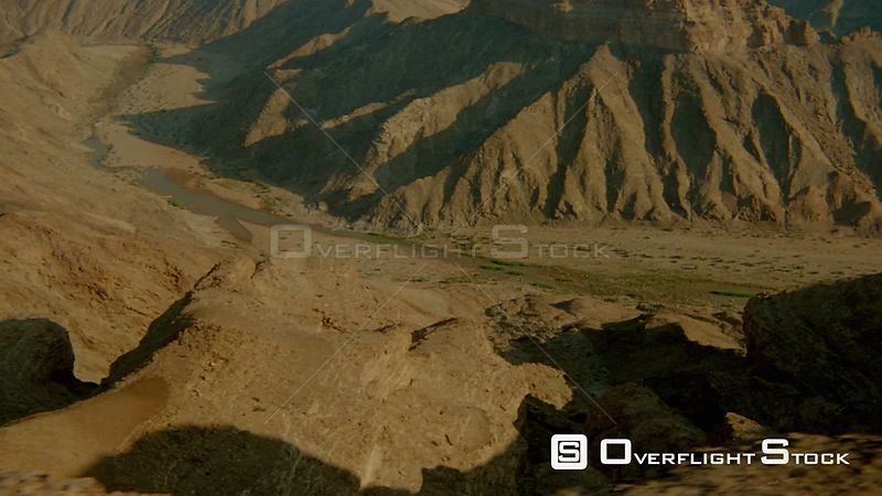Aerial wide angle shot top and sides of mountains with river and river banks below, river curves left Fish River Canyon Namibia