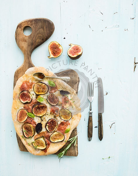 Rustic homemade pizza with figs, prosciutto and mozzarella cheese on dark wooden serving board over light blue backdrop. Top ...