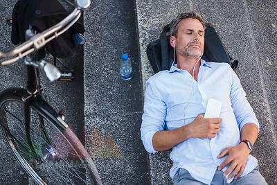Man with closed eyes lying on stairs with cell phone and earbuds next to bicycle