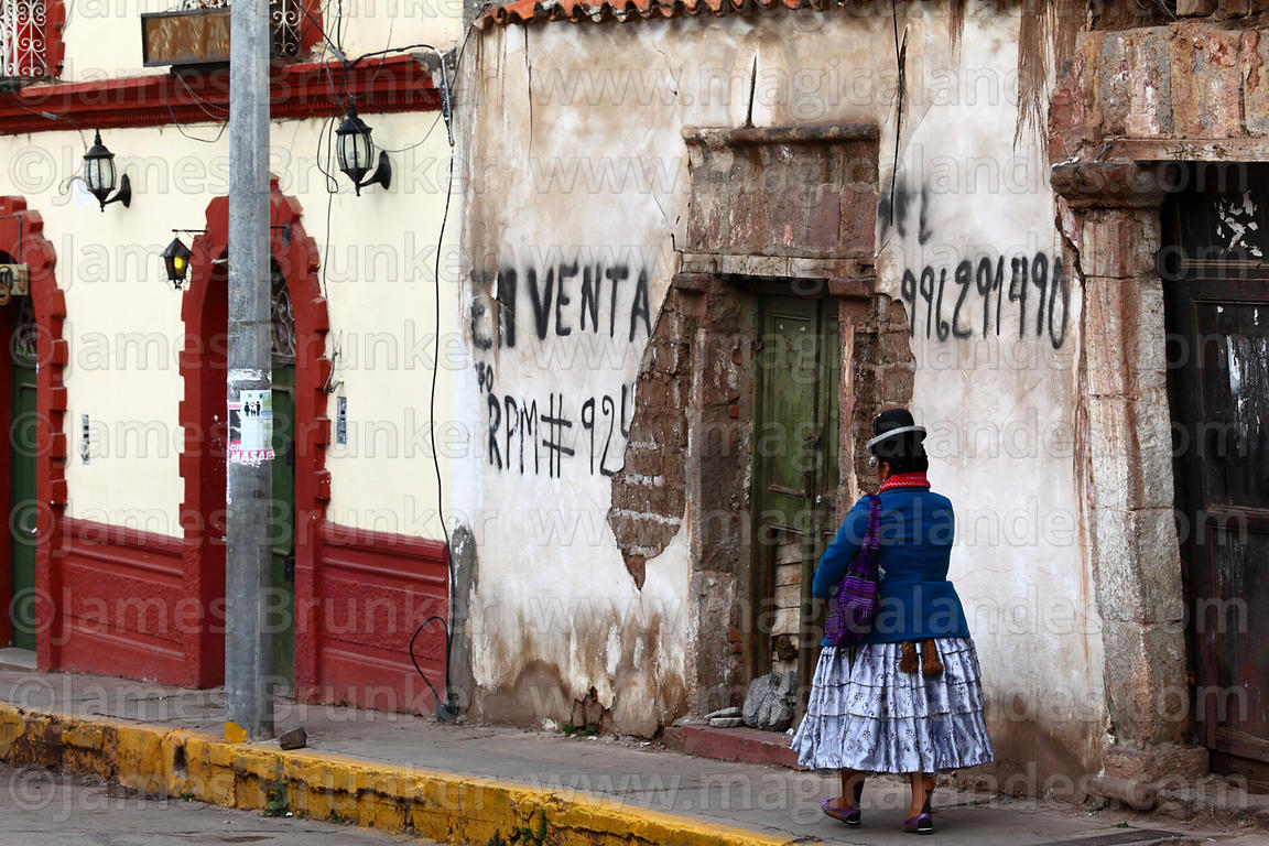 Aymara woman walking past old house for sale, Plaza de Armas, Puno, Peru