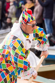Man in Harlequin suit rowing in the Venice Carnival Water Parade