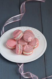 Pink macarons with buttercream filling on white plate