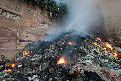 A trash fire burns along the Ganges River, Varanasi, India.
