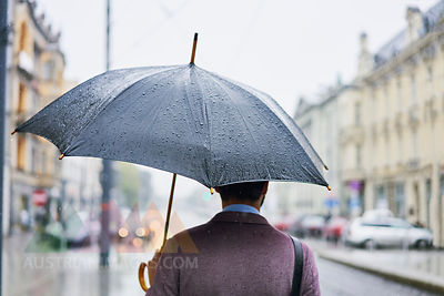 Back view of businessman in the city with umbrella on a rainy day