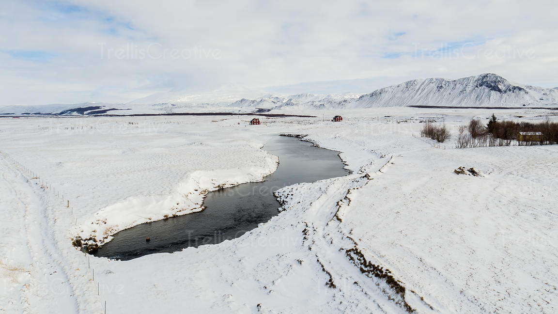 Aerial view of two red cabins along a volcanic river in a snowy scene in Iceland