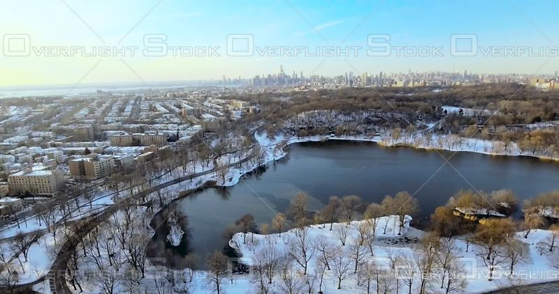 Aerial Over Prospect Park and Pond Snow Brooklyn Manhattan in Background NYC