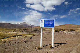Sign next to gauge measuring flow of River Guallatiri, Guallatiri volcano in background, Las Vicuñas National Reserve, Region...