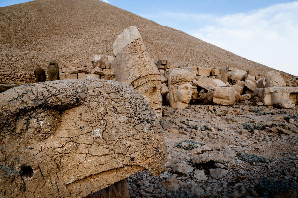 The west terrace of Mount Nemrut with heads of the colossal statues and the tumulus.  Head of guardian eagle in foreground wi...
