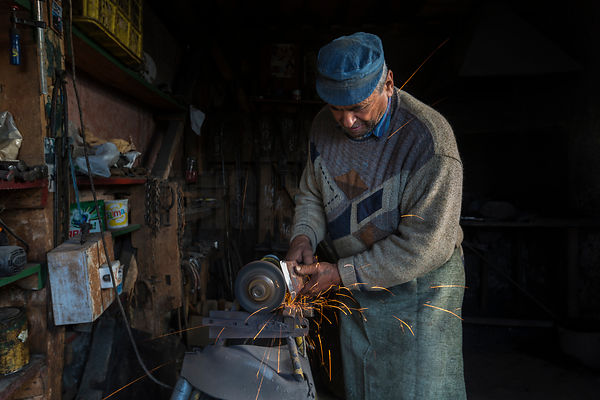 Portrait of a Blacksmith Sharpening an Axe Head