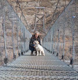 Dog and woman travelling and exploring a bridge