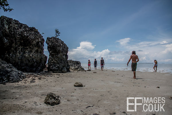 People Walking On A Tropical Beach With Interesting Rock Formations