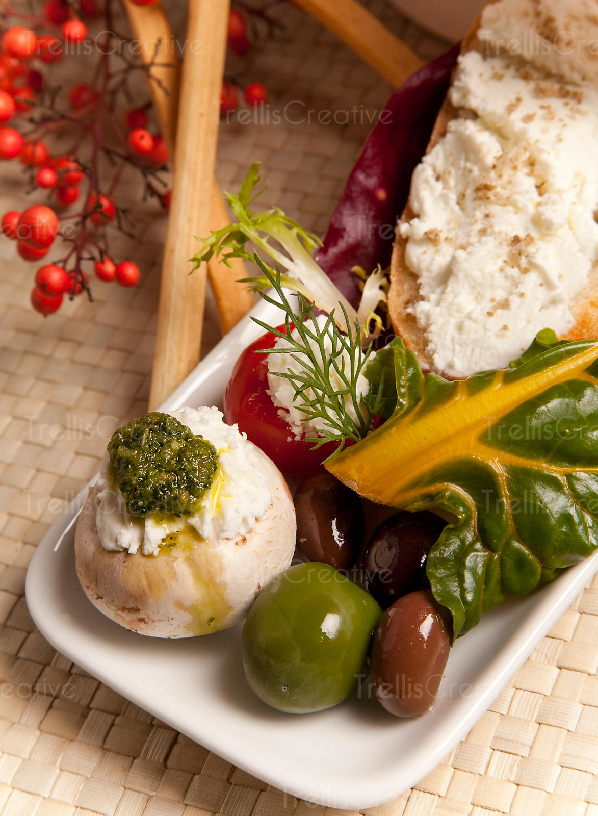 Appetizer plate of chard, olives, peppers, mushrooms and goat cheese on a white platter