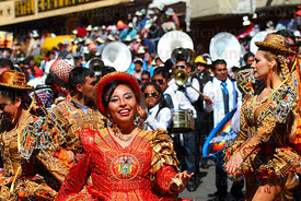 Portrait of caporales dancer with the Bolivian coat of arms on her blouse at Gran Poder festival, La Paz, Bolivia