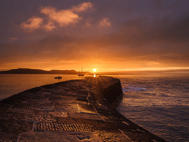 Golden sunrise with Irene anchored off The Cobb in Lyme Regis, Dorset, UK