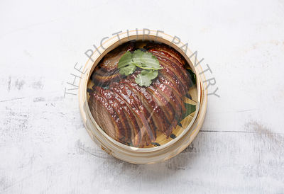Sliced Peking Duck and cilantro in bamboo steamer on white background