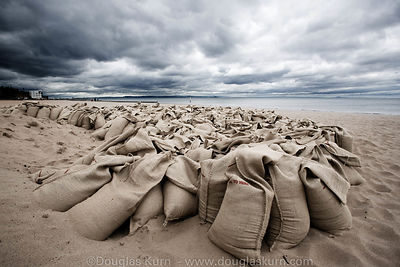 Limited edition Giclée fine art print of  sandbags on Portobello Beach under a cloudy sky.