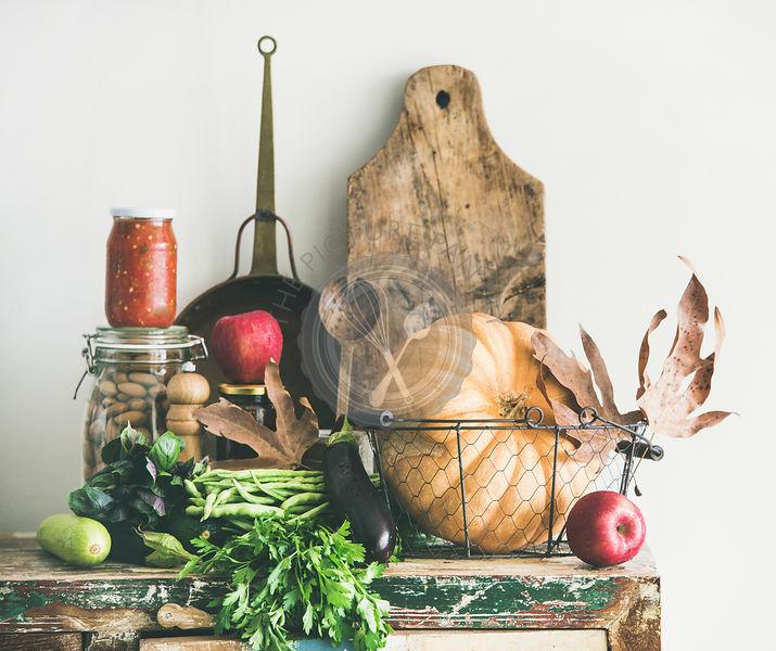 Autumn seasonal food ingredients and kitchen utensils over wooden cupboard
