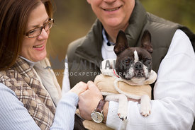 owners holding and smiling at small dog in coat
