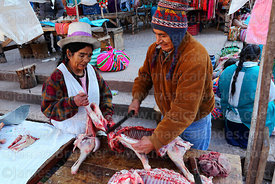 Couple cutting up lamb for sale at Pisac market, Sacred Valley, Cusco Region, Peru
