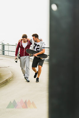 Two happy friends walking with skateboards