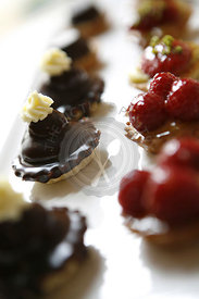 Sweet cakes from a patisserie. Mini cakes.  Chocolate and cream pie, strawberry tarts
