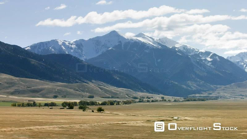 Golden hay fields in the Madison valley sit in the shadow of the snow-capped Madison mountains in southwestern Montana