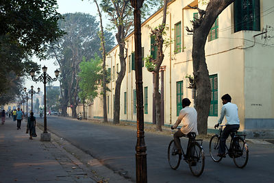 India - Chandannagar - Pedestrians and cyclists on the Strand, the main French style avenue on the banks of the Hooghley Rive