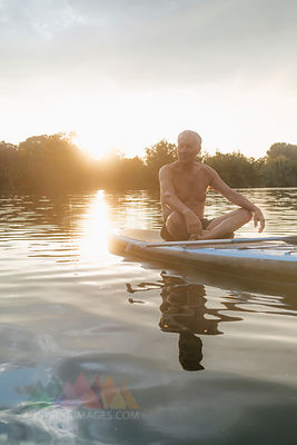 Senior man sitting on SUP board at sunset