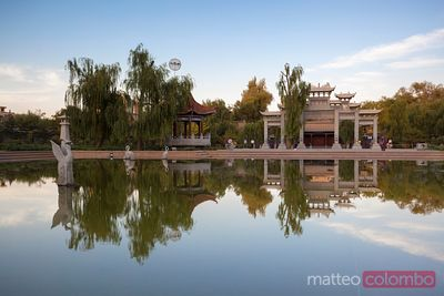 Chinese pagoda reflected in lake at sunset