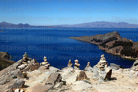 Cairns next to a high point of path overlooking Kuna Bay and Peninsula, Sun Island, Lake Titicaca, Bolivia