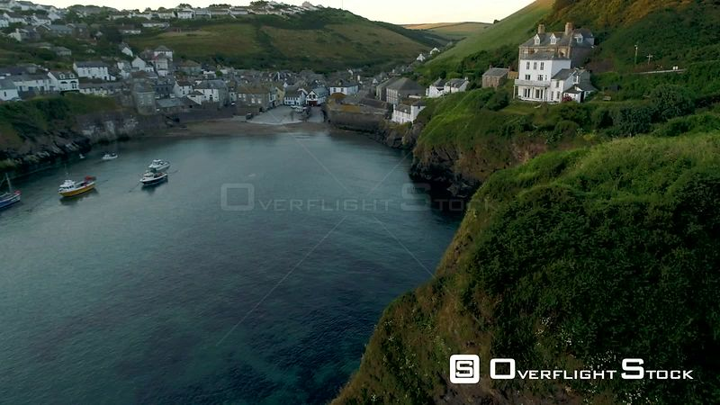 Drone rises from behind cliffs with the  village Port Isaac in Cornwall behind.