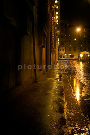 An atmospheric image of a wet empty street in Rome, Italy, at night.