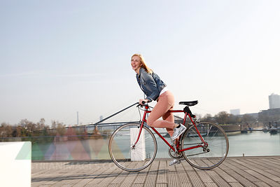 Germany, Duesseldorf, happy blond woman riding bicycle in front of Rhine River