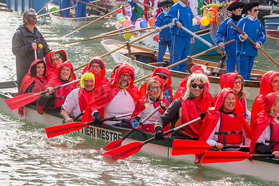 Boat with smiling Men and Women wearing red Capes and Hoods in the Venice Carnival Water Parade on the Rio di Cannaregio Canal