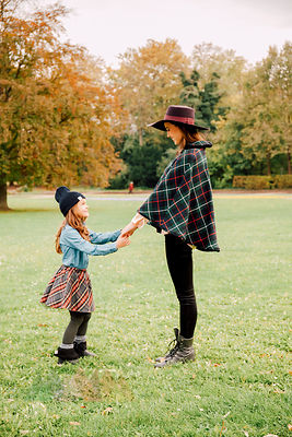 Young woman and little girl standing face to face on a meadow in autumn holding hands