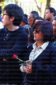 Devotee holding a red rose and Huawei smartphone during Good Friday procession, La Paz, Bolivia