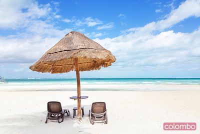 Sunshade and lounge chairs on sandy beach in the Caribbean