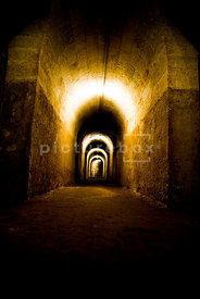 An atmospheric, low perspective image of a darkly lit underground tunnel / bunker, stretching off into the distance.
