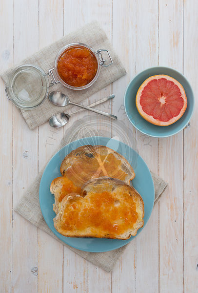 Pink Grapefruit Marmalade on toast, with a half pink grapefruit.