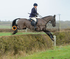 Emilie Chandler jumping a hedge next to Mrs Greenall's Covert - The Belvoir Hunt at Goadby Hall 24/12