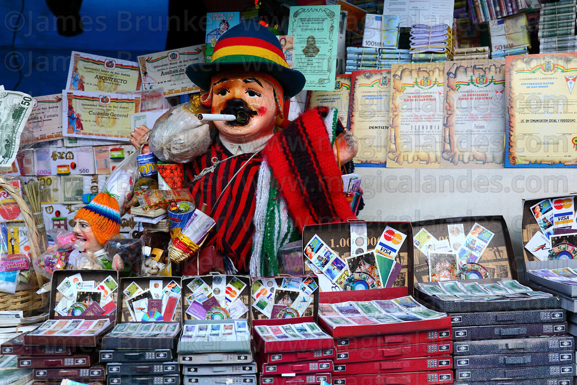 Ekeko and miniature suitcases with travel documents for sale on market stall, Alasitas festival, La Paz, Bolivia